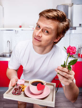 Man in white t-shirt standing in the kitchen with  breakfast and a rose photo