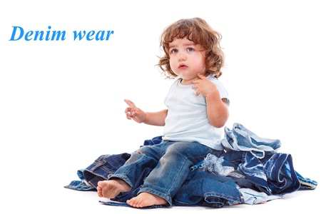 Lovely curly child sitting on the jeans pile photo