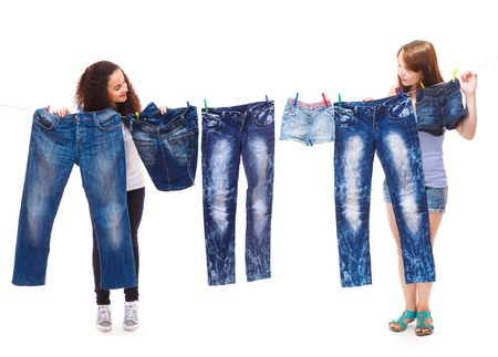 denim skirt: Two teenage friends  hanging up fashionable jeans wear