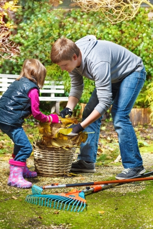 Father and daughter picking up yellow leaves  Foto de archivo