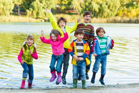 elementary students: Kids in rubber boots jumping Stock Photo