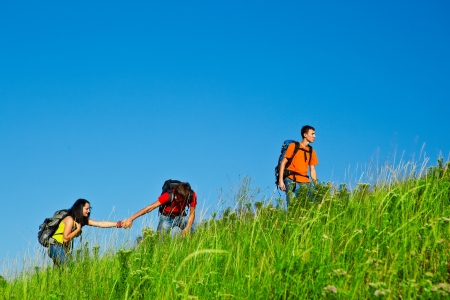 Friends with backpacks on climbing the summer hill photo