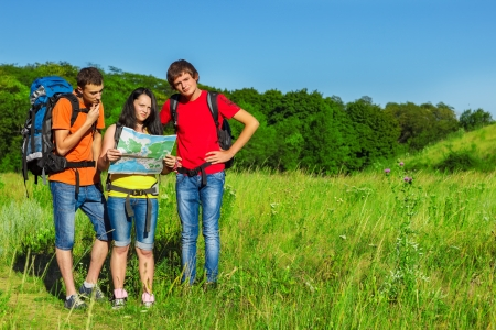 Teenage friends backpacking with a map photo