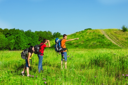 Group of teenage backpackers observing the area photo