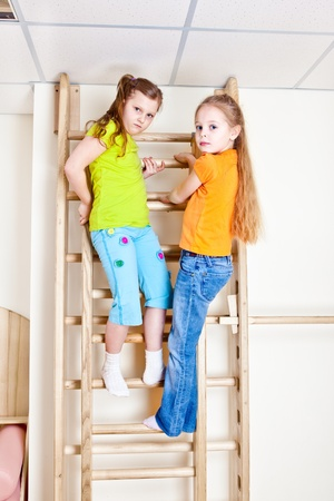 Two girls on the wooden wall bars Stock Photo - 20434659