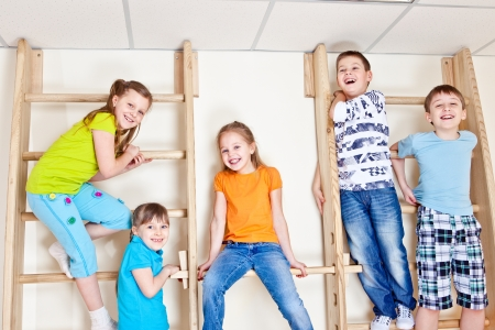 wall bars: Group of laughing basic school students sitting on wall bars