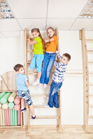 wall bars: Active kids climbing on the wooden wall bars Stock Photo
