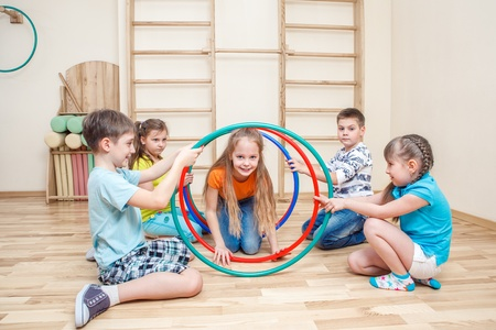 Cheerful kids playing with hoops in a school gym photo