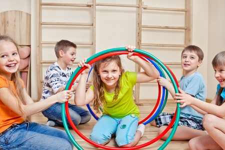 Laughing active children holding hoops photo