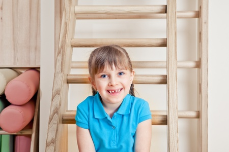 Pretty smiling primary school student in a gym photo