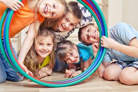 girotondo bambini: Cinque bambini allegri guardando attraverso i cerchi