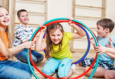girotondo bambini: Ridere bambini che giocano in una palestra Archivio Fotografico