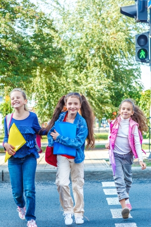 school aged: Basic school students crossing the road Stock Photo