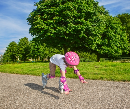 Preschool girl with inline roller skates on, falling down photo