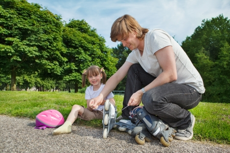 Father helping preschool daughter with her inline roller skates photo
