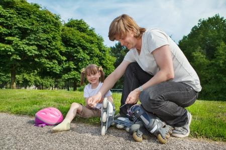patines: Padre ayudando a su hija preescolar con sus patines en l�nea Foto de archivo