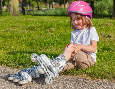 Girl with helmet on but without protective knee pads crying photo