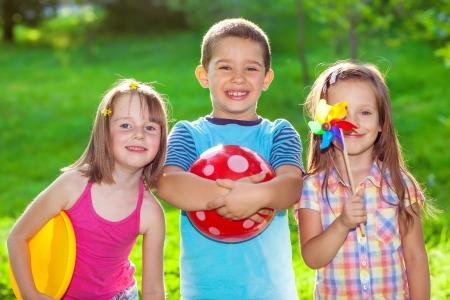Trois enfants souriants dans un parc d'été