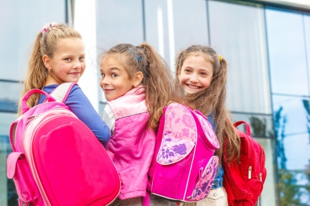 Portrait of three smiling friendly students going to school Banco de Imagens