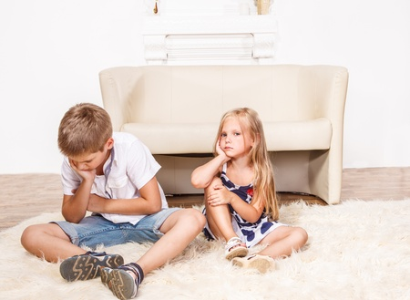angry child: Angry siblings sitting on the carpet