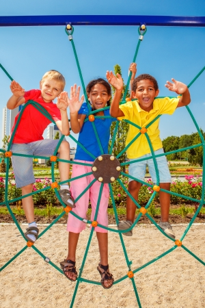 Cheerful friends climbing the net at a city playground Foto de archivo