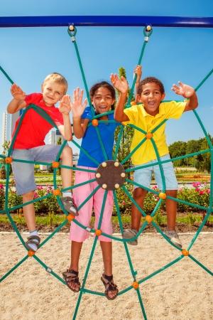 Joyeuses amis escalade le net à une aire de jeux de la ville Banque d'images