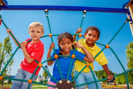 Friends climbing the net at the playground Stock Photo