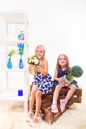 little girl dress: Two beautiful long haired girls sit on wooden boxes