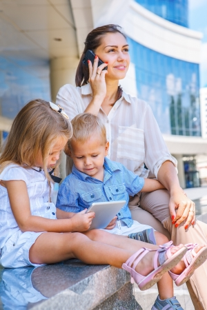Busy mother with mobile phone, kids sit with electronic tablet photo