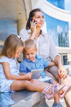 Mère occupée avec le téléphone portable, les enfants s'asseoir avec tablette électronique