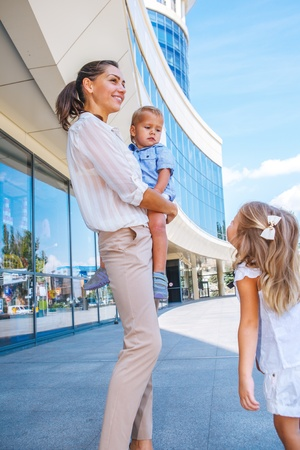 Smiling businesswoman with her two kids near office building photo
