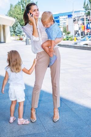 Jeune femme avec deux enfants parler au téléphone