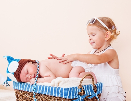 Elder sister taking care of a sleeping infant Stock Photo