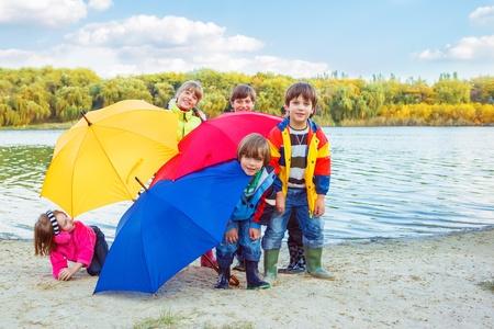 botas de lluvia: Grupo de niños escondiéndose detrás de los paraguas
