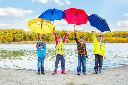 Boys and girls holding umbrellas high above photo