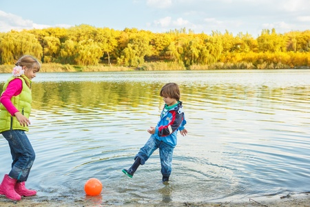 Brother and sister playing with ball in an autumnal pond photo