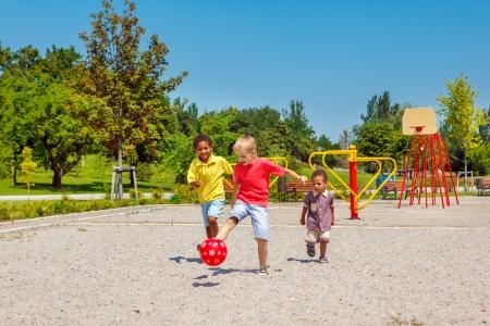 Les enfants heureux en cours d'exécution avec un ballon sur le terrain de jeu