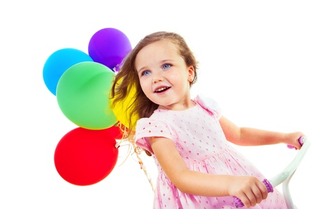 Portrait of a cheerful little girl on a bike, with colorful balloons behind photo