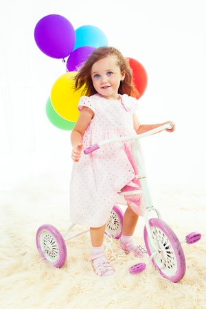 three wheeler: Sweet preschool girl on a white and pink vintage kids three wheeler