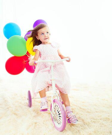niños en bicicleta: Se preguntó la niña en una bicicleta de tres ruedas, mirando hacia arriba