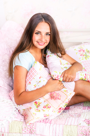 Smiling young woman sitting in bed in the morning photo