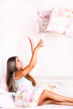 Happy beautiful young woman playing with pillows photo