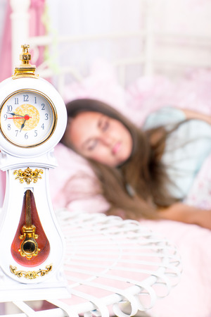 bed sheet: Clock on the table and a girl sleeping in bed
