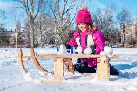 Preschool girl sitting beside sledges and making snowballs photo