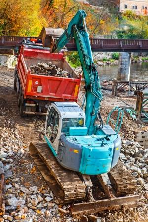 360-degree excavator loading stones to the truck Stock Photo