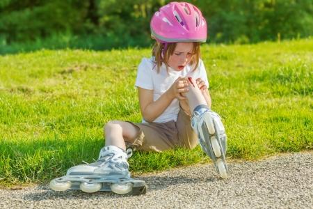 Preschool skateroll beginner looking at her bleeding knee