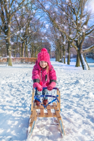 Active girl playing in a winter park photo