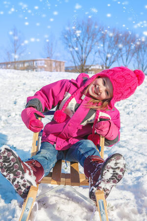 Laughing kid on a winter hill in a park photo
