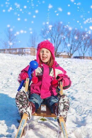 Girl in winter clothes sits on sledges with a snowball maker photo