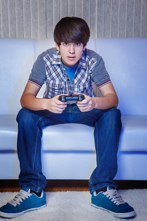 Teenage gamer in with a joystick photo